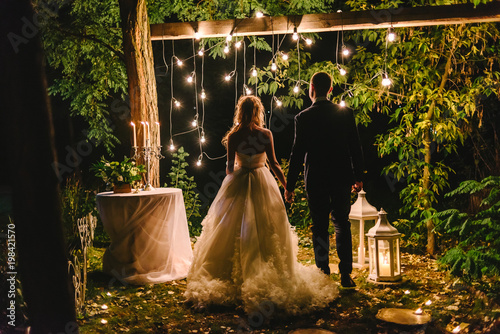 Night wedding ceremony with candles, lanterns and lamps on tree. Bride and groom holding hands on background of baulb lights, back view. Beautiful young couple standing under a tree at night