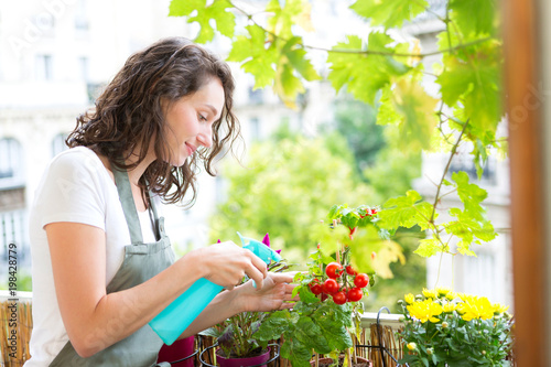 Foto Murales Young woman watering tomatoes on her city balcony garden - Nature and ecology theme