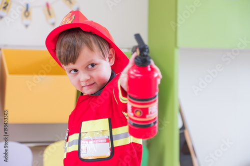 Foto Murales Caucasian boy kid dress up to fireman and use speaker at roll play classroom,Kindergarten preschool education concept