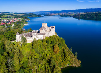 Poland. Medieval Castle in Niedzica, built in 14th century, artificial Czorsztyn Lake and far view of the ruins of Czorsztyn castle, Aerial view in the morning