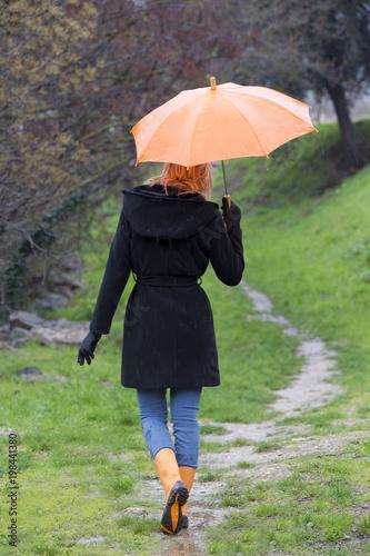 femme qui marche dans l'herbe avec un parapluie