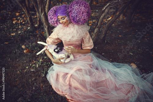Beautiful model wearing pink dress is posing in a creative wig