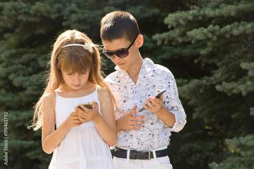 Children with phone on the street. Gadgets in the modern world. girl and boy are friends.