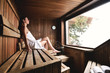 Leinwanddruck Bild - A beautiful woman wearing a white towel takes a sauna: The sauna is made of wood with a large window with a view of the snow. Concept of: relax, vacation, wellness center.