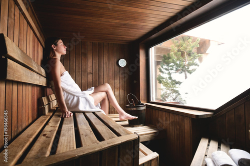 Leinwanddruck Bild A beautiful woman wearing a white towel takes a sauna: The sauna is made of wood with a large window with a view of the snow. Concept of: relax, vacation, wellness center.