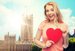 love, travel, tourism, valentines day and people concept - smiling young woman or teenage girl with blank red heart shape over london city background