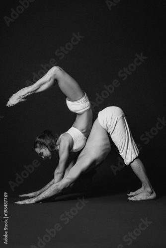 Monochrome portrait of beautiful sporty couple: woman and man in white clothes doing yoga asanas together indoor