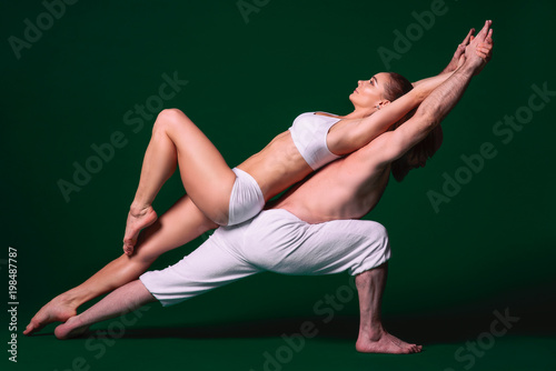 Beautiful sporty woman and man in white clothes doing yoga asanas together indoor on green background