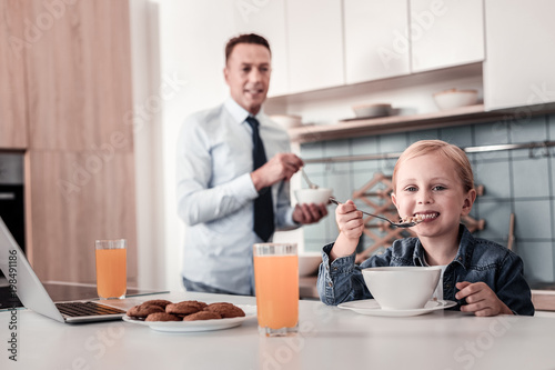 I like it. Silhouette of conscious father that expressing positivity while cooking breakfast and looking at his daughter