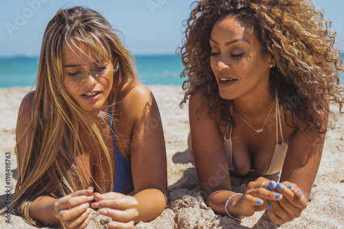 Content relaxing multiethnic women sunbathing while lying on hot hat of beach with ocean on background and talking.
