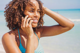 Laughing young pretty ethnic woman sitting at the ocean and looking away while talking on smartphone.