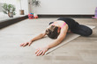 Woman makes the yoga exercise on the mat, indoors