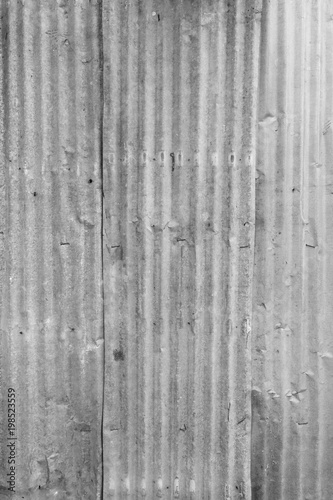 Faded and corrugated iron metal construction site wall texture background in black and white.