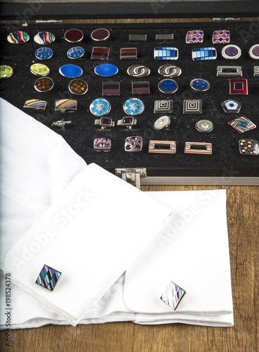colorful cufflinks on the black and wooden background - 198524378