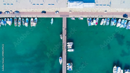 Plexiglas Cyprus Aerial bird's eye view of Zygi fishing village port, Larnaca, Cyprus. Bird eye view of aligned fish boats moored in the harbour, docked yachts, pier, wave breaker rocks near Limassol from above.