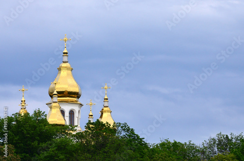 Foto op Plexiglas Kiev Golden domes of an orthodox church among blossoming trees against a background of a cloudy blue sky