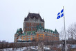 View of Frontenac  (Chateau de Frontenac, in French) in winter under the snow with a Quebec flag waiving. The Château Frontenac is a grand hotel in Quebec City.