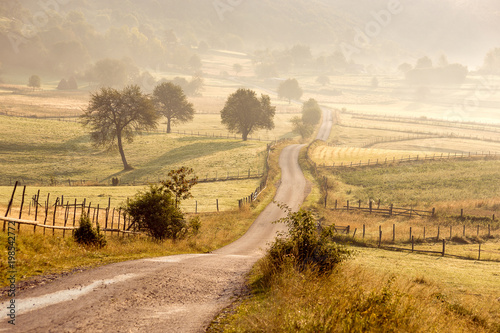 Foto op Canvas Beige Beautiful Rural Village Landscape with Road at Morning