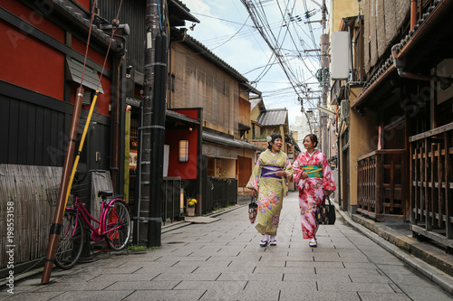 Fotobehang Smalle straatjes Women in traditional dress that call kimono, are walking on the stone pavement in culture street at Gion, Kyoto, Japan.