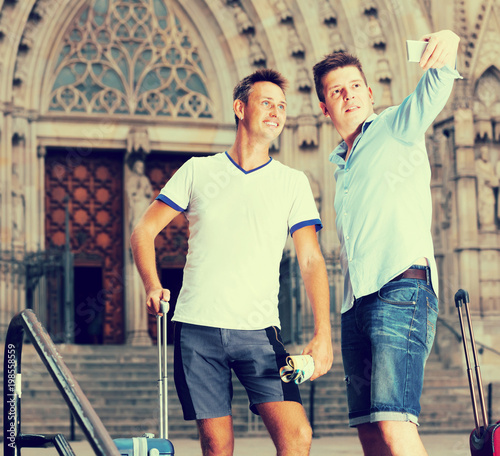 Male couple with luggage doing selfie at travel