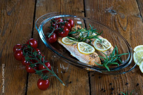Salmon. Two juicy salmon steaks in roast pan with herb decoration on rustic oak table. © Chodyra Mike