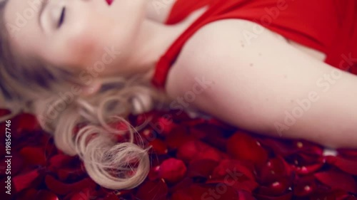 Beautiful blonde girl lies in a lot of red roses. Red lips and gentle makias. Girl in a red dress. Valentine's Day. Light studio. Lies with her eyes closed, touches her hair.