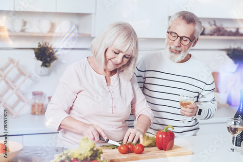 Healthy lifestyle. Cheerful delighted aged couple standing in the kitchen and making vegetable salad while expressing gladness - 198573121