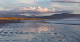 Couple walking in evening glow of the sun on Inch beach in County Kerry
