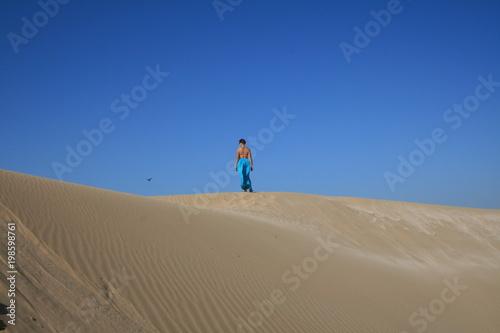 Keuken foto achterwand Marokko Young woman in blue skirt in sand dunes