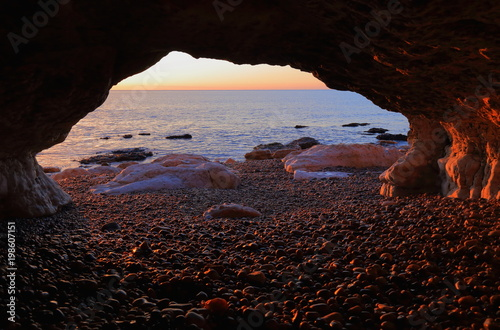 Foto op Plexiglas Ochtendgloren Sunrise over the Jurassic Coast natural World Heritage Site, seen from the sea cave near village of Beer in Devon