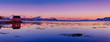 Landscape with beautiful winter lake, red rorbu house and snowy mountains at sunset at Lofoten Islands in Northern Norway. Panoramic view