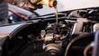 Leinwandbild Motiv Mechanic fills the engine with engine oil
