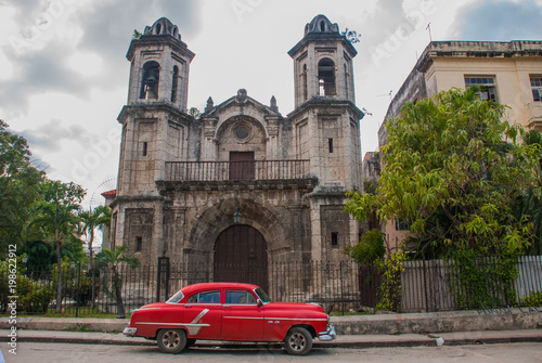 Foto op Canvas Scooter Retro American car of red color near the Catholic Cathedral. Havana. Cuba