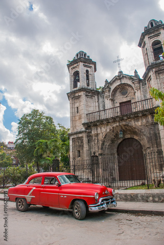 Fotobehang Scooter Retro American car of red color near the Catholic Cathedral. Havana. Cuba