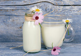 Tasty and healthy: fresh milk in bottle and glass with flowers in front of old, blue, wooden board :) - 198625741