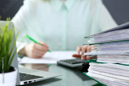 Bookkeeper or financial inspector  making report, calculating or checking balance. Binders with papers closeup. Audit and tax service concept. Green colored image background  © rogerphoto