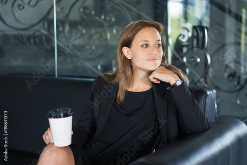 Closeup portrait of content young beautiful brown-haired woman looking away, holding disposable cup and sitting on sofa in hotel lobby. Coffee break concept. Front view.