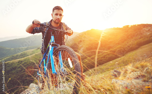 cycling. young man with bicycle on nature in mountains - 198660143