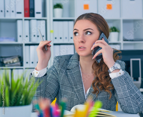 Young serious Caucasian businesswoman sitting at desk in office, speaking on the phone.
