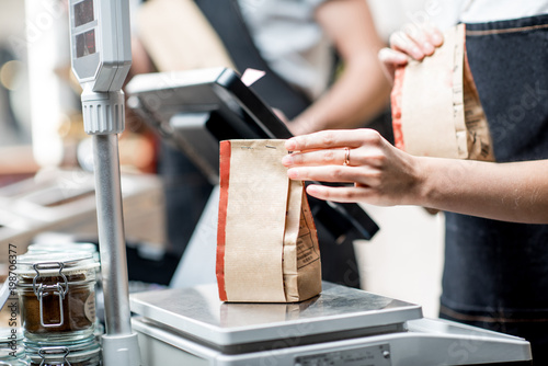 Weighing paper bag with coffee beans in the coffee store - 198706377