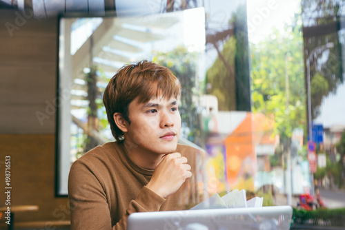 Handsome asian man using laptop sitting on wooden table in coffee shop with a cup of coffee - 198716513