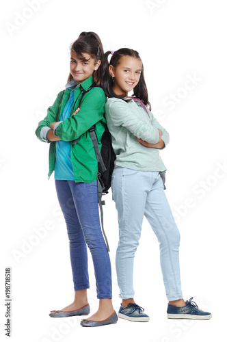 Two schoolgirls wearing casual clothes standing back to back full length picture