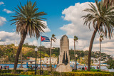 Cuba flag and statue of Jesus Christ on a hill overlooking the port and the bay of Havana.