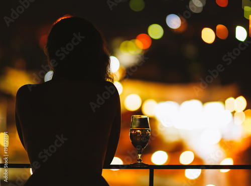 Fotobehang Kuala Lumpur Silhouette of naked woman on the balcony with a glass of wine on the background of a night city