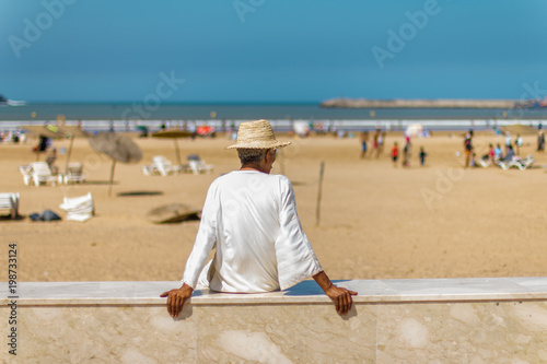 Keuken foto achterwand Marokko Man in a white tunic and a straw hat sitting on the beach.September 2, 2012 in Essaouira, Morocco, Africa