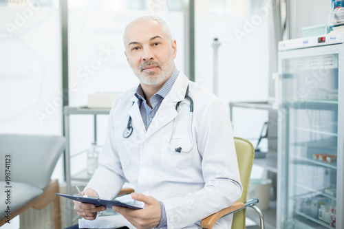 Confident mature clinician in uniform sitting in armchair while working with documents in clinics