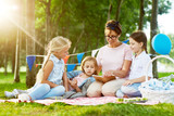 Affectionate woman and charming girls relaxing on green lawn in park while reading tales together - 198743902