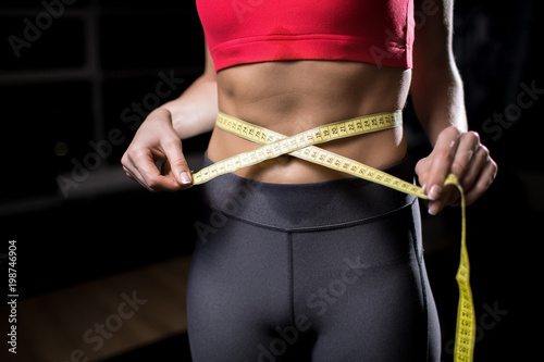 Mid-section of fit girl with measuring tape around her waist after hard workout in gym