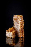 bright honeycombs with honey reflecting on black background, rustic food photography