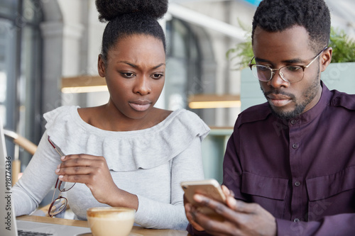 Serious dark skinned female and male business partners check notification on smart phone, work on report at laptop computer, sit in coffee shop have concentrated looks. People, technology, partnership